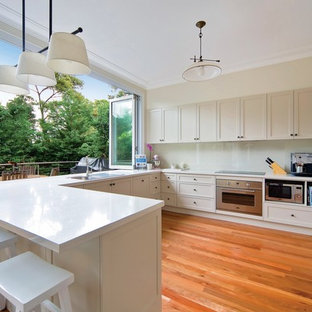 This is an example of a transitional u-shaped eat-in kitchen in Sydney with white cabinets, white splashback, stainless steel appliances, medium hardwood floors, white benchtop, a drop-in sink, shaker cabinets, glass sheet splashback, a peninsula and red floor.