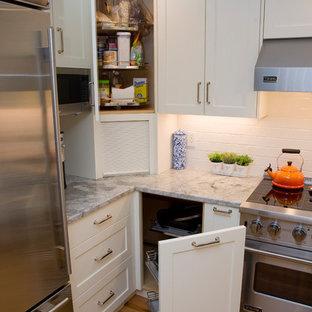 ボストンの中くらいのトランジショナルスタイルのおしゃれなキッチン (アンダーカウンターシンク、落し込みパネル扉のキャビネット、白いキャビネット、珪岩カウンター、白いキッチンパネル、サブウェイタイルのキッチンパネル、シルバーの調理設備、無垢フローリング、グレーのキッチンカウンター) の写真