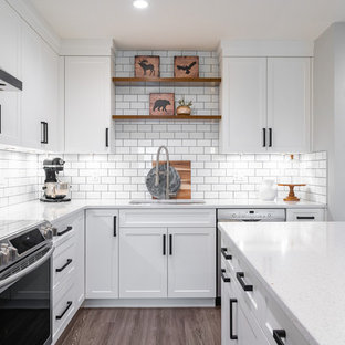 Design ideas for a mid-sized transitional l-shaped eat-in kitchen in Vancouver with an undermount sink, white cabinets, quartz benchtops, white splashback, subway tile splashback, stainless steel appliances, with island, brown floor, white benchtop, shaker cabinets and vinyl floors.