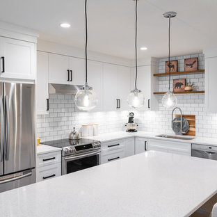 Photo of a mid-sized transitional l-shaped eat-in kitchen in Vancouver with an undermount sink, white cabinets, quartz benchtops, white splashback, subway tile splashback, stainless steel appliances, with island, brown floor, white benchtop, shaker cabinets and vinyl floors.