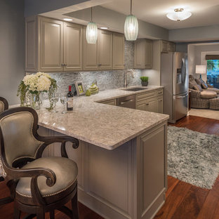 Eat-in kitchen - mid-sized traditional l-shaped medium tone wood floor and brown floor eat-in kitchen idea in Other with an undermount sink, raised-panel cabinets, gray cabinets, granite countertops, gray backsplash, stone tile backsplash, stainless steel appliances and no island