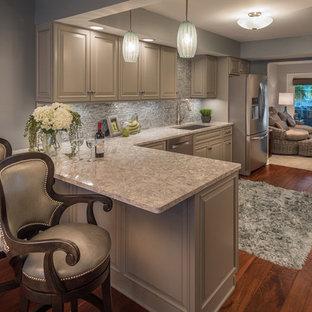 Inspiration för mellanstora klassiska kök, med en undermonterad diskho, luckor med upphöjd panel, grå skåp, granitbänkskiva, grått stänkskydd, stänkskydd i stenkakel, rostfria vitvaror, mellanmörkt trägolv och brunt golv