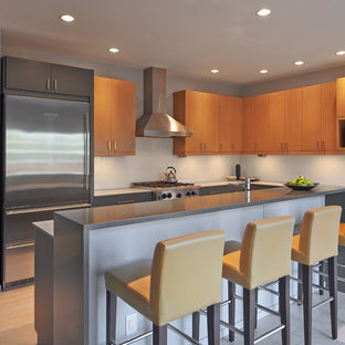 Design ideas for a mid-sized contemporary l-shaped open plan kitchen in Seattle with with island, flat-panel cabinets, light wood cabinets, quartz benchtops, blue splashback, glass sheet splashback, stainless steel appliances, an undermount sink and bamboo floors.