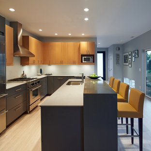 This is an example of a mid-sized contemporary l-shaped open plan kitchen in Seattle with with island, flat-panel cabinets, quartz benchtops, stainless steel appliances, an undermount sink, bamboo floors, light wood cabinets, blue splashback and glass sheet splashback.