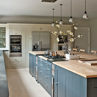 Photo of a large contemporary separate kitchen in Gloucestershire with shaker cabinets, grey cabinets, wood benchtops, stainless steel appliances and an island.