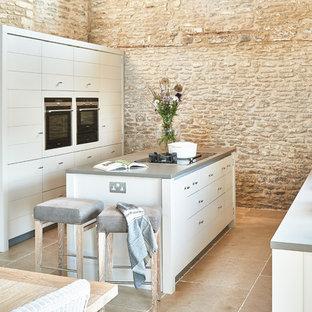 Cette photo montre une cuisine américaine nature avec un évier 1 bac, des portes de placard grises, un îlot central, un sol beige et un plan de travail gris.