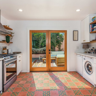 ロサンゼルスの中サイズのトラディショナルスタイルのおしゃれなキッチン (エプロンフロントシンク、シェーカースタイル扉のキャビネット、白いキャビネット、クオーツストーンカウンター、白いキッチンパネル、サブウェイタイルのキッチンパネル、シルバーの調理設備の、セメントタイルの床、赤い床、白いキッチンカウンター) の写真