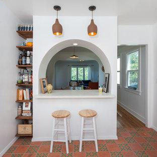 ロサンゼルスの中くらいのトラディショナルスタイルのおしゃれなキッチン (エプロンフロントシンク、シェーカースタイル扉のキャビネット、白いキャビネット、クオーツストーンカウンター、白いキッチンパネル、サブウェイタイルのキッチンパネル、シルバーの調理設備、セメントタイルの床、赤い床、白いキッチンカウンター) の写真