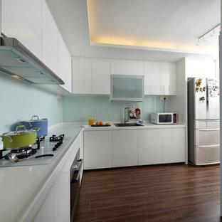 シンガポールの中くらいのアジアンスタイルのおしゃれなキッチン (シングルシンク、フラットパネル扉のキャビネット、白いキャビネット、人工大理石カウンター、白いキッチンパネル、ガラス板のキッチンパネル、カラー調理設備、磁器タイルの床、アイランドなし) の写真