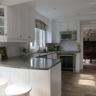 This is an example of a mid-sized traditional u-shaped eat-in kitchen in Ottawa with a double-bowl sink, shaker cabinets, white cabinets, solid surface benchtops, white splashback, subway tile splashback, stainless steel appliances, ceramic floors, a peninsula and beige floor.