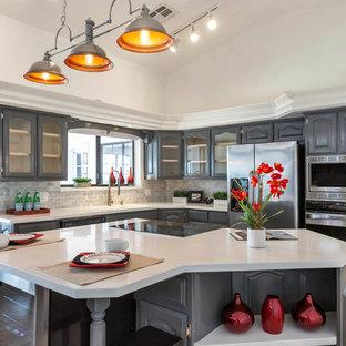 Esempio di una cucina a L tradizionale con ante grigie, paraspruzzi grigio, paraspruzzi con piastrelle diamantate, elettrodomestici in acciaio inossidabile, isola, pavimento beige, top bianco e ante di vetro