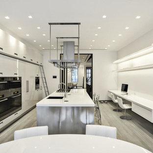 ニューヨークの中くらいのモダンスタイルのおしゃれなキッチン (白いキャビネット、ガラスカウンター、アンダーカウンターシンク、フラットパネル扉のキャビネット、白いキッチンパネル、ガラス板のキッチンパネル、シルバーの調理設備、淡色無垢フローリング、ベージュの床) の写真