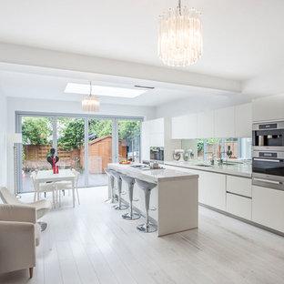 Imagen de cocina de galera, contemporánea, con armarios con paneles lisos, puertas de armario blancas, electrodomésticos de acero inoxidable, suelo de madera pintada y una isla