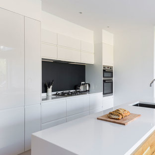 Example of a large minimalist galley open concept kitchen design in London with an integrated sink, flat-panel cabinets, white cabinets, quartzite countertops, paneled appliances, an island and black backsplash