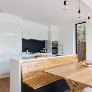 Foto de cocina de galera, contemporánea, grande, abierta, con armarios con paneles lisos, puertas de armario blancas, encimera de cuarcita, electrodomésticos con paneles, suelo de madera en tonos medios y una isla