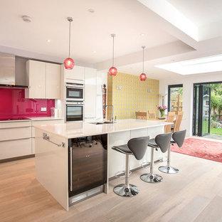 Inspiration för moderna kök, med en undermonterad diskho, släta luckor, vita skåp, rosa stänkskydd, rostfria vitvaror, ljust trägolv och en köksö
