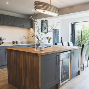 This is an example of a large classic galley kitchen/diner in Essex with a submerged sink, shaker cabinets, grey cabinets, wood worktops, stainless steel appliances, medium hardwood flooring, an island, brown floors and beige worktops.