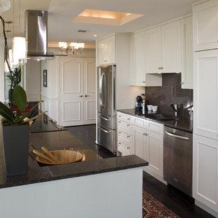 Inredning av ett modernt litet kök, med rostfria vitvaror, en dubbel diskho, luckor med infälld panel, vita skåp, stänkskydd i sten, granitbänkskiva, grått stänkskydd, en köksö och svart golv