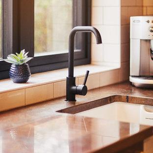サセックスの小さいインダストリアルスタイルのおしゃれなキッチン (エプロンフロントシンク、シェーカースタイル扉のキャビネット、青いキャビネット、銅製カウンター、白いキッチンパネル、サブウェイタイルのキッチンパネル、シルバーの調理設備の) の写真