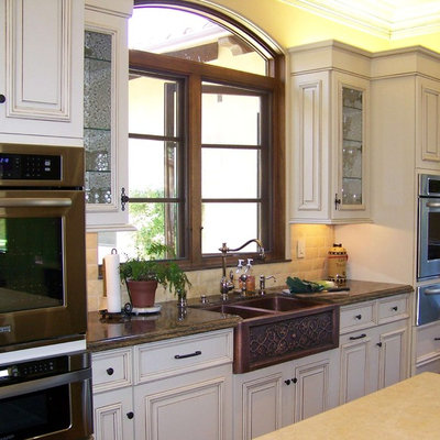 Example of a large classic l-shaped ceramic tile and beige floor open concept kitchen design in San Diego with stainless steel appliances, a farmhouse sink, marble countertops, white cabinets, beige backsplash, stone tile backsplash, raised-panel cabinets and two islands