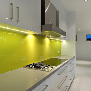 This is an example of a large modern galley kitchen pantry in Brisbane with a double-bowl sink, yellow splashback, porcelain splashback, stainless steel appliances, porcelain floors and no island.