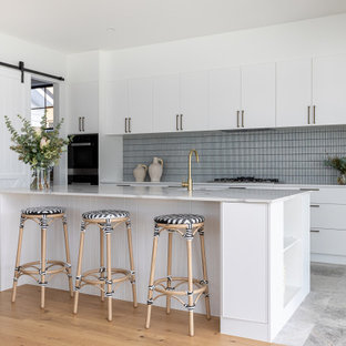 Inspiration for a contemporary galley kitchen in Brisbane with an undermount sink, flat-panel cabinets, white cabinets, grey splashback, subway tile splashback, with island, grey floor and white benchtop.