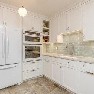 ニューヨークの中くらいのインダストリアルスタイルのおしゃれなキッチン (アンダーカウンターシンク、シェーカースタイル扉のキャビネット、白いキャビネット、クオーツストーンカウンター、青いキッチンパネル、ガラスタイルのキッチンパネル、白い調理設備、磁器タイルの床、アイランドなし、マルチカラーの床、白いキッチンカウンター) の写真