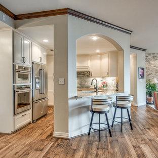 ダラスの中サイズのサンタフェスタイルのおしゃれなコの字型キッチン (アンダーカウンターシンク、インセット扉のキャビネット、白いキャビネット、御影石カウンター、緑のキッチンパネル、石スラブのキッチンパネル、シルバーの調理設備の、無垢フローリング、茶色い床、グレーのキッチンカウンター) の写真