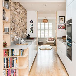 Imagen de cocina de galera, escandinava, de tamaño medio, con armarios con paneles lisos, salpicadero de ladrillos, suelo de bambú y suelo beige