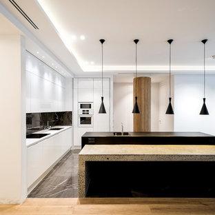 Новые идеи обустройства дома: угловая кухня в современном стиле с плоскими фасадами, белыми фасадами, черным фартуком, белой техникой, белой столешницей, врезной раковиной, островом и серым полом