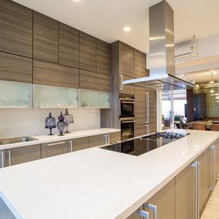 Imagen de cocina de galera, contemporánea, de tamaño medio, con armarios con paneles lisos, puertas de armario beige, encimera de acrílico, electrodomésticos de acero inoxidable y una isla