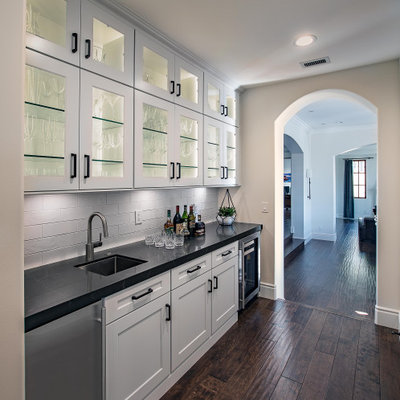 Inspiration for a transitional single-wall dark wood floor and brown floor kitchen pantry remodel in Orange County with an undermount sink, glass-front cabinets, white cabinets, white backsplash, subway tile backsplash, no island and black countertops