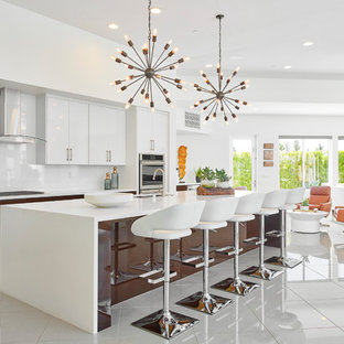 Midcentury modern open concept kitchen photos - Inspiration for a 1950s white floor open concept kitchen remodel in Orange County with an undermount sink, flat-panel cabinets, white cabinets, white backsplash, glass sheet backsplash, an island and white countertops