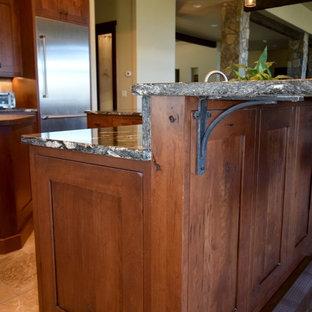 デンバーのラスティックスタイルのおしゃれなキッチン (エプロンフロントシンク、シェーカースタイル扉のキャビネット、濃色木目調キャビネット、御影石カウンター、ベージュキッチンパネル、トラバーチンのキッチンパネル、シルバーの調理設備、トラバーチンの床、ベージュの床) の写真