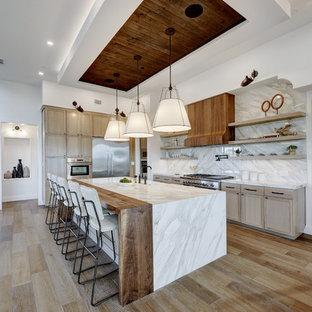 Inredning av ett modernt vit vitt l-kök, med en rustik diskho, skåp i shakerstil, skåp i ljust trä, vitt stänkskydd, rostfria vitvaror, mellanmörkt trägolv, en köksö och brunt golv