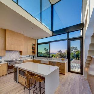 ロサンゼルスの大きいコンテンポラリースタイルのおしゃれなキッチン (エプロンフロントシンク、落し込みパネル扉のキャビネット、中間色木目調キャビネット、クオーツストーンカウンター、シルバーの調理設備、白いキッチンカウンター、淡色無垢フローリング、ベージュの床、グレーのキッチンパネル) の写真