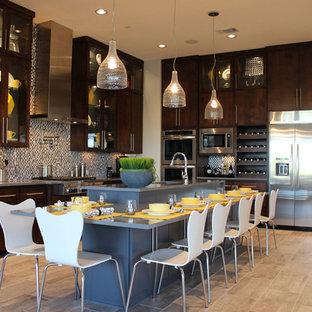 オースティンの広いモダンスタイルのおしゃれなキッチン (アンダーカウンターシンク、フラットパネル扉のキャビネット、濃色木目調キャビネット、人工大理石カウンター、マルチカラーのキッチンパネル、シルバーの調理設備、セラミックタイルの床) の写真