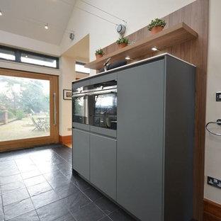 Idéer för att renovera ett mellanstort funkis kök, med grå skåp, svarta vitvaror, en köksö, en dubbel diskho, släta luckor, träbänkskiva, svart stänkskydd, stänkskydd i trä, mellanmörkt trägolv och svart golv