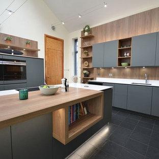 Foto på ett mellanstort funkis kök, med grå skåp, svarta vitvaror, en köksö, en dubbel diskho, släta luckor, träbänkskiva, svart stänkskydd, stänkskydd i trä, mellanmörkt trägolv och svart golv
