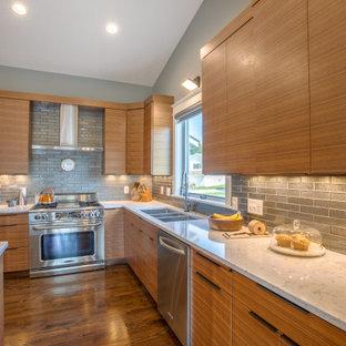 Idée de décoration pour une cuisine américaine vintage en U de taille moyenne avec un évier encastré, un placard à porte plane, des portes de placard en bois brun, un plan de travail en quartz modifié, une crédence grise, une crédence en carrelage métro, un électroménager en acier inoxydable, un sol en bois brun, un îlot central, un sol beige et un plan de travail blanc.