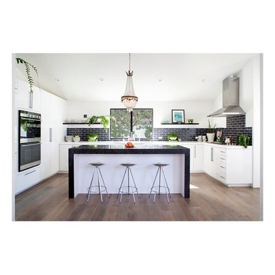 Eat-in kitchen - mid-sized modern u-shaped dark wood floor and brown floor eat-in kitchen idea in Orange County with an undermount sink, flat-panel cabinets, white cabinets, solid surface countertops, black backsplash, subway tile backsplash, stainless steel appliances and an island