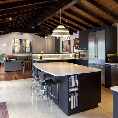Mountain style u-shaped open concept kitchen photo in Vancouver with a drop-in sink, black cabinets, flat-panel cabinets and stainless steel appliances