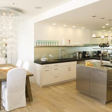 Sleek, elegant kitchen with frosted glass backsplash, staniless steel island