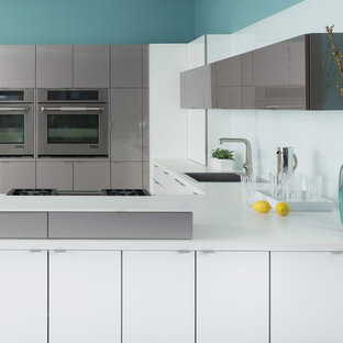Example of a trendy u-shaped kitchen design in Newark with a drop-in sink, flat-panel cabinets, white cabinets, white backsplash, glass sheet backsplash, stainless steel appliances and a peninsula