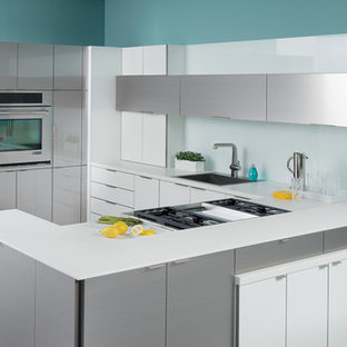 Kitchen - contemporary u-shaped kitchen idea in Chicago with a drop-in sink, flat-panel cabinets, white cabinets, white backsplash, glass sheet backsplash, stainless steel appliances and a peninsula