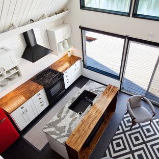 ポートランドの中サイズのエクレクティックスタイルのおしゃれなキッチン (白いキャビネット、木材カウンター、黒い調理設備、アンダーカウンターシンク、シェーカースタイル扉のキャビネット、白いキッチンパネル、磁器タイルのキッチンパネル、濃色無垢フローリング、黒い床) の写真