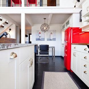 ポートランドの中サイズのエクレクティックスタイルのおしゃれなキッチン (アンダーカウンターシンク、シェーカースタイル扉のキャビネット、白いキャビネット、木材カウンター、白いキッチンパネル、磁器タイルのキッチンパネル、黒い調理設備、濃色無垢フローリング、黒い床) の写真