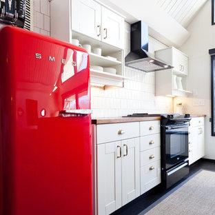 ポートランドの中くらいのエクレクティックスタイルのおしゃれなアイランドキッチン (白いキャビネット、木材カウンター、黒い調理設備、白いキッチンパネル、アンダーカウンターシンク、シェーカースタイル扉のキャビネット、磁器タイルのキッチンパネル、濃色無垢フローリング、黒い床) の写真