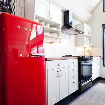 Example of a mid-sized eclectic dark wood floor and black floor kitchen design in Portland with white cabinets, wood countertops, black appliances, an island, white backsplash, an undermount sink, shaker cabinets and porcelain backsplash