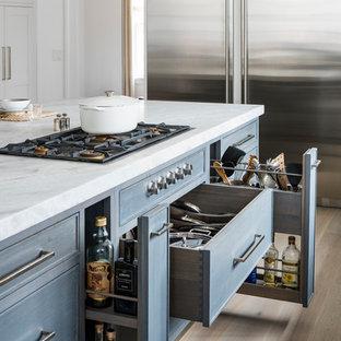 Idee per una cucina chic con ante blu, elettrodomestici in acciaio inossidabile, parquet chiaro e isola